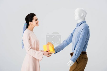 Photo for Beautiful girl taking gift box from mannequin isolated on grey - Royalty Free Image
