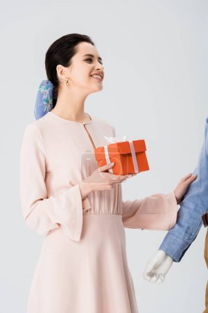 Photo for Beautiful girl with gift box smiling near mannequin isolated on grey - Royalty Free Image