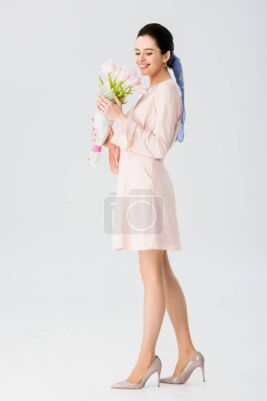 Photo for Beautiful young woman holding bouquet of tulips and smiling isolated on grey - Royalty Free Image