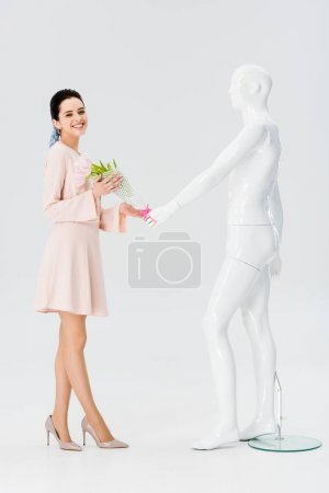 Photo for Beautiful smiling girl with mannequin and flower bouquet isolated on grey - Royalty Free Image