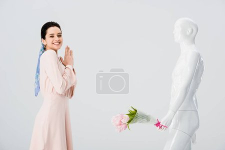 Photo for Beautiful excited girl and mannequin with flower bouquet isolated on grey - Royalty Free Image