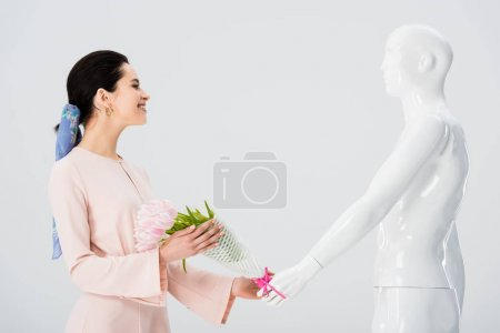Photo for Beautiful girl taking flower bouquet from mannequin isolated on grey - Royalty Free Image