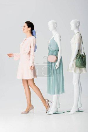 Photo pour Belle fille de sourire posant avec des mannequins dans des robes sur le gris - image libre de droit