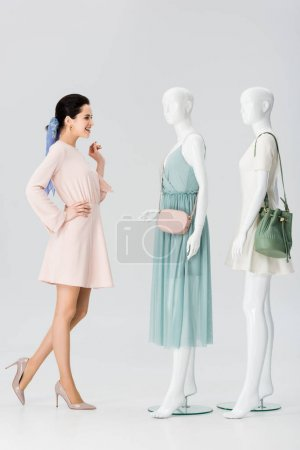 Photo for Beautiful smiling girl looking at mannequins in dresses on grey - Royalty Free Image