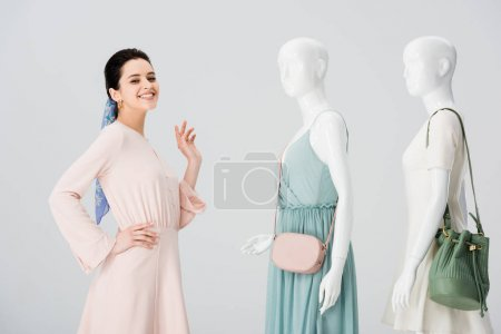Photo for Beautiful happy girl posing with mannequins in dresses isolated on grey - Royalty Free Image
