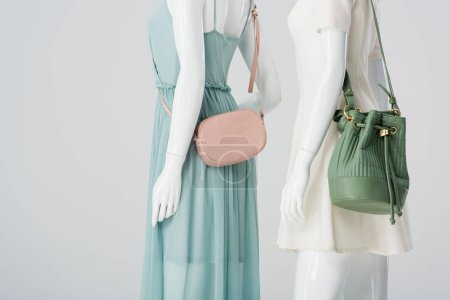 mannequins with bags and dresses isolated on grey