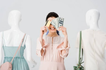 Photo for Beautiful girl near mannequins covering face with money and credit card isolated on grey - Royalty Free Image