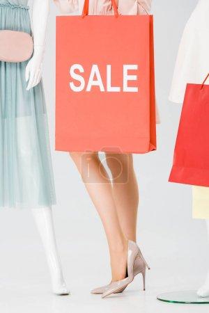 Photo pour Vue recadrée de jeune femme avec sac à provisions avec mot vente sur gris - image libre de droit