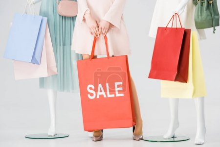 Photo for Partial view of young woman with sale lettering on shopping bag near mannequins on grey - Royalty Free Image