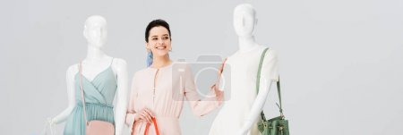 Photo for Panoramic shot of beautiful girl posing with mannequins in dresses isolated on grey - Royalty Free Image