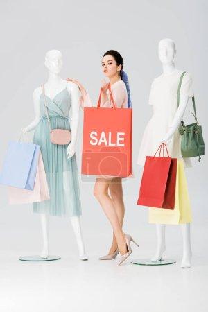 Photo pour Jolie jeune femme avec lettrage de vente sur le sac à provisions près des mannequins sur le gris - image libre de droit