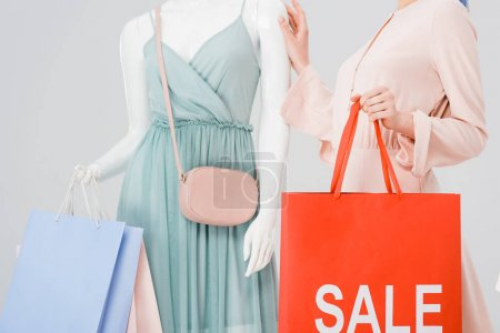 Photo for Cropped view of young woman holding shopping bag with sale word near mannequin isolated on grey - Royalty Free Image