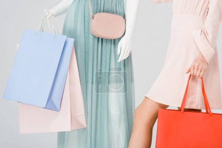 Photo for Cropped view of young woman and mannequin with shopping bags isolated on grey - Royalty Free Image