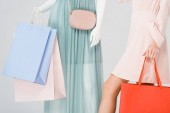 Cropped view of young woman and mannequin with shopping bags isolated on grey