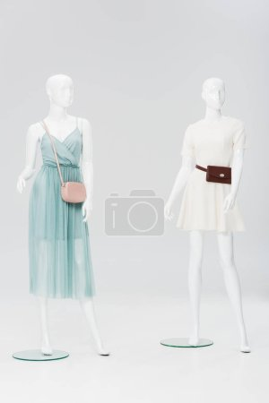 Photo for Plastic mannequins with bags and dresses isolated on grey - Royalty Free Image