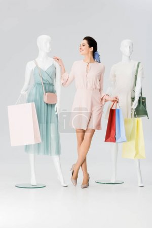 Photo for Beautiful girl with shopping bags near mannequins on grey - Royalty Free Image