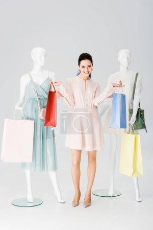 Photo pour Belle fille heureuse avec des sacs à provisions près des mannequins sur le gris - image libre de droit