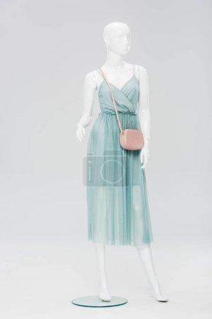 Foto de Plastic mannequin with bag and dress isolated on grey - Imagen libre de derechos