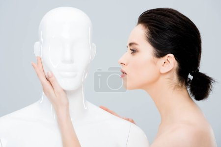 Photo for Attractive young woman posing with mannequin isolated on grey - Royalty Free Image