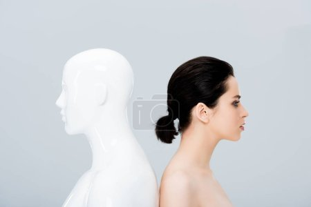 Photo for Beautiful naked young woman posing with mannequin isolated on grey - Royalty Free Image
