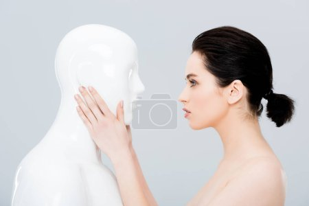 Photo for Beautiful young woman touching plastic mannequin isolated on grey - Royalty Free Image