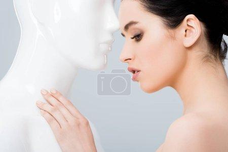 Foto de Hermosa mujer joven tocando maniquí aislado en gris - Imagen libre de derechos