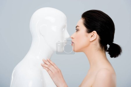 Photo for Beautiful young woman looking at plastic mannequin isolated on grey - Royalty Free Image