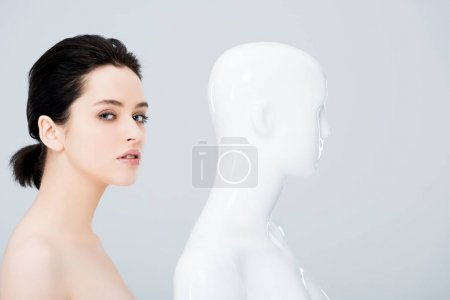 Photo for Beautiful young woman looking at camera and posing with mannequin isolated on grey - Royalty Free Image