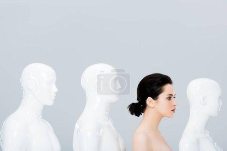 Foto de Nude young woman posing in row of mannequins isolated on grey - Imagen libre de derechos