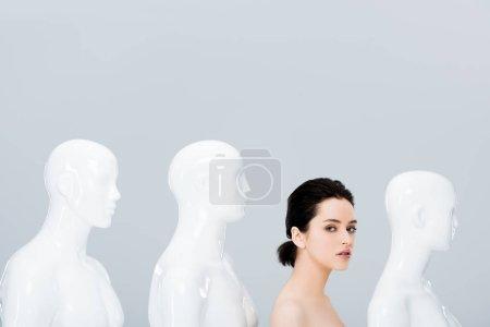 Photo pour Belle fille nue posant dans la rangée des mannequins et regardant l'appareil-photo isolé sur le gris - image libre de droit