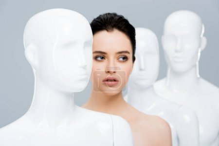 Photo for Beautiful girl posing in row of mannequins isolated on grey - Royalty Free Image