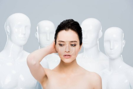 Photo for Beautiful young woman posing near mannequins isolated on grey - Royalty Free Image