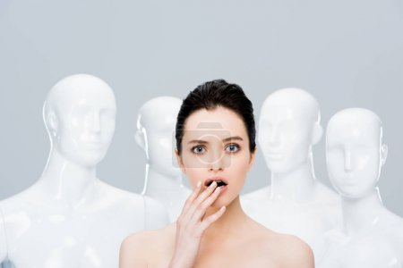 Photo for Beautiful surprised girl posing near mannequins isolated on grey - Royalty Free Image