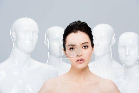 Photo pour Belle jeune femme nue regardant l'appareil-photo près des mannequins isolés sur le gris - image libre de droit