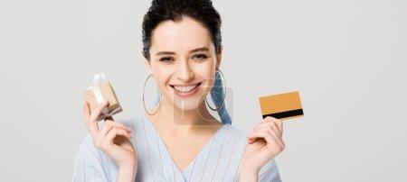 Foto de Foto panorámica de hermosa chica elegante sosteniendo caja de regalo y tarjeta de crédito aislada en gris - Imagen libre de derechos