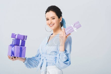 Photo for Smiling stylish girl holding gift boxes and looking at camera isolated on grey - Royalty Free Image