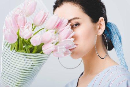 Photo pour Belle fille élégante dans des boucles d'oreilles avec le bouquet des tulipes d'isolement sur le gris - image libre de droit