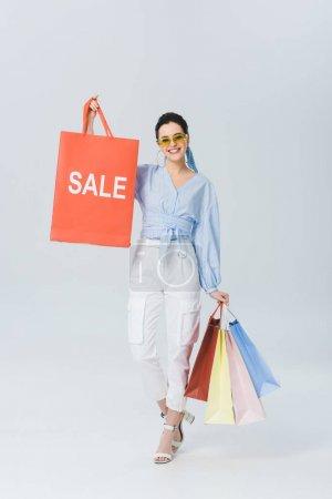 Photo pour Sac à provisions de fixation de fille élégante de sourire avec le mot de vente sur le gris - image libre de droit