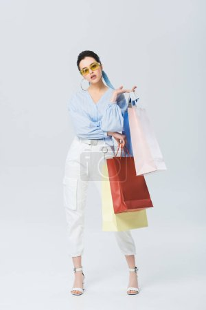 Photo for Beautiful stylish girl with shopping bags on grey - Royalty Free Image