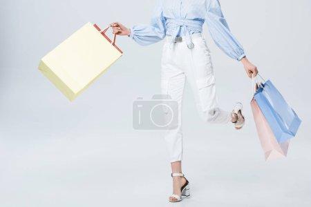 Photo pour Vue recadrée d'une fille élégante marchant avec des sacs à provisions sur gris - image libre de droit