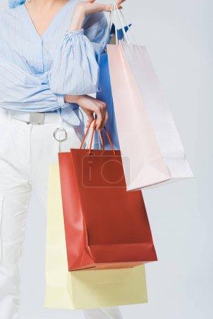 vue partielle de fille élégante avec des sacs à provisions isolés sur gris