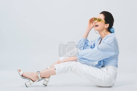 Photo for Beautiful stylish girl in sunglasses posing and laughing on grey - Royalty Free Image