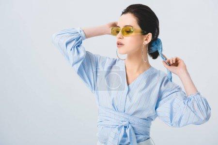 Photo pour Belle jeune femme élégante dans des lunettes de soleil posant d'isolement sur le gris - image libre de droit