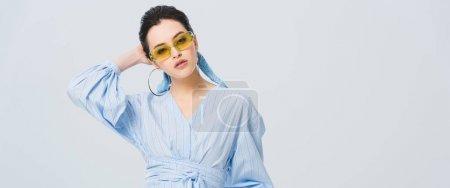 Photo pour Tir panoramique de belle fille élégante dans des lunettes de soleil posant d'isolement sur le gris - image libre de droit