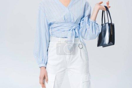 Photo pour Vue recadrée de jeune femme élégante avec le sac posant d'isolement sur le gris - image libre de droit