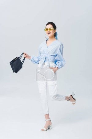 Photo for Beautiful stylish young woman in sunglasses holding bag and smiling on grey - Royalty Free Image