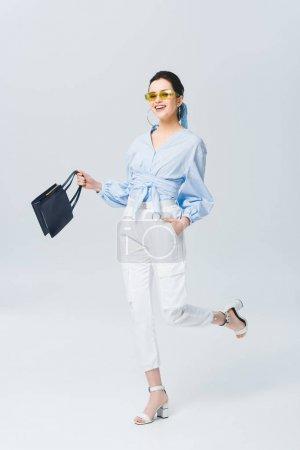 Photo pour Belle jeune femme élégante dans le sac de fixation de lunettes de soleil et souriant sur le gris - image libre de droit