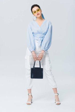 Photo pour Belle fille élégante avec sac regardant l'appareil-photo et posant sur le gris - image libre de droit