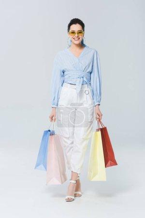 Photo pour Belle fille de sourire avec des sacs à provisions regardant l'appareil-photo sur le gris - image libre de droit