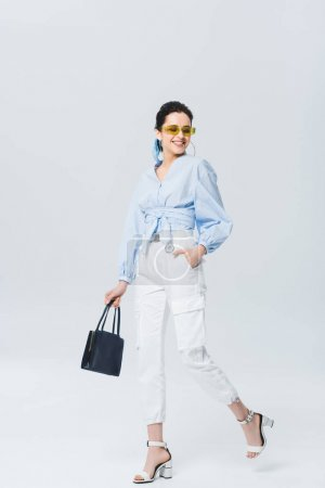 Photo pour Belle fille élégante marchant et souriant sur le gris - image libre de droit